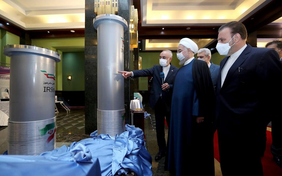 Iranian President Hassan Rouhani, second from right, listens to the head of the Atomic Energy Organisation of Iran Ali Akbar Salehi while visiting an exhibition of Iran's new nuclear achievements in Tehran - Iranian Presidency Office via AP