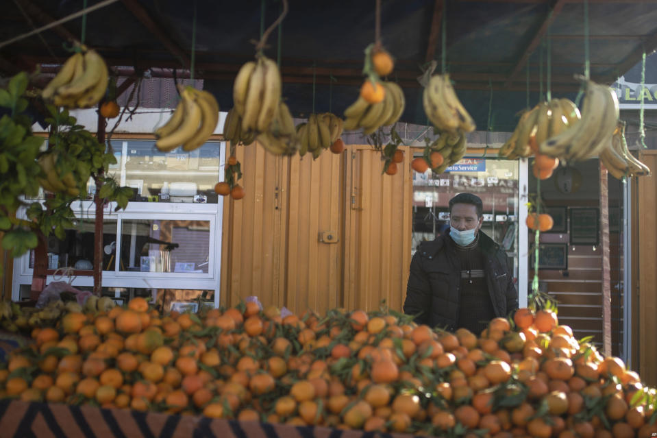 A fruit vendor wearing a face mask waits for clients in a daily market in Dakhla, Western Sahara, Monday, Dec. 21, 2020. U.S. plans to open a consulate in Western Sahara mark a turning point for the disputed and closely policed territory. U.S. recognition of Morocco's authority over the land frustrates indigenous Sahrawis seeking independence. But others see the future U.S. consulate as a major boost for Western Sahara cities like Dakhla. (AP Photo/Mosa'ab Elshamy)