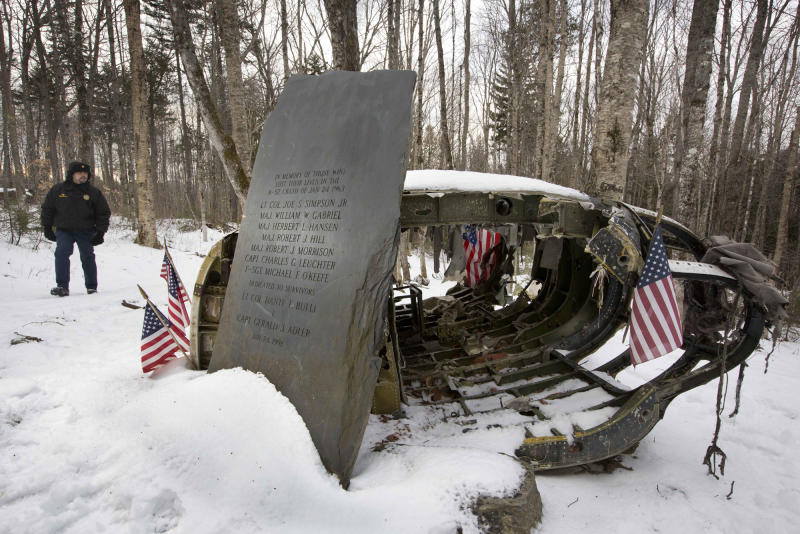 HOLD FOR STORY MOVING MAY 25 BY DAVID SHARP FILE - In this Dec. 14, 2012 file photo, Greenville, Maine, Police Chief Jeff Pomerleau views a monument next to wreckage from a B-52 bomber on Elephant Mountain near Greenville, Maine. The plane's 40-foot-tall vertical stabilizer had snapped off, and the plane crash in January 1963 killed seven of the nine people on board. Air Force personnel from around the country gathered in Greenville, Saturday, May 25, 2013 to remember the deadly crash. (AP Photo/Robert F. Bukaty, File)
