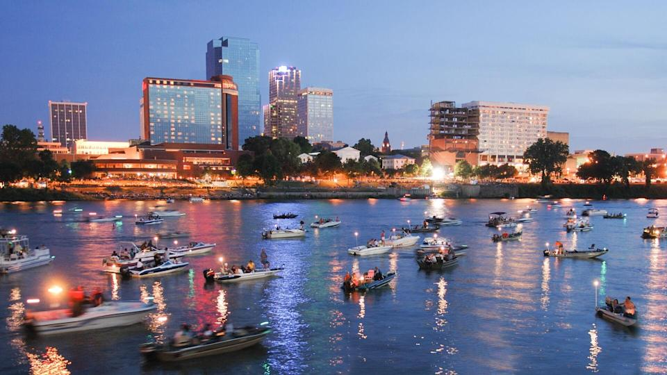 """Skyline of Little Rock, Arkansas, with Arkansas River full of boats in foreground."