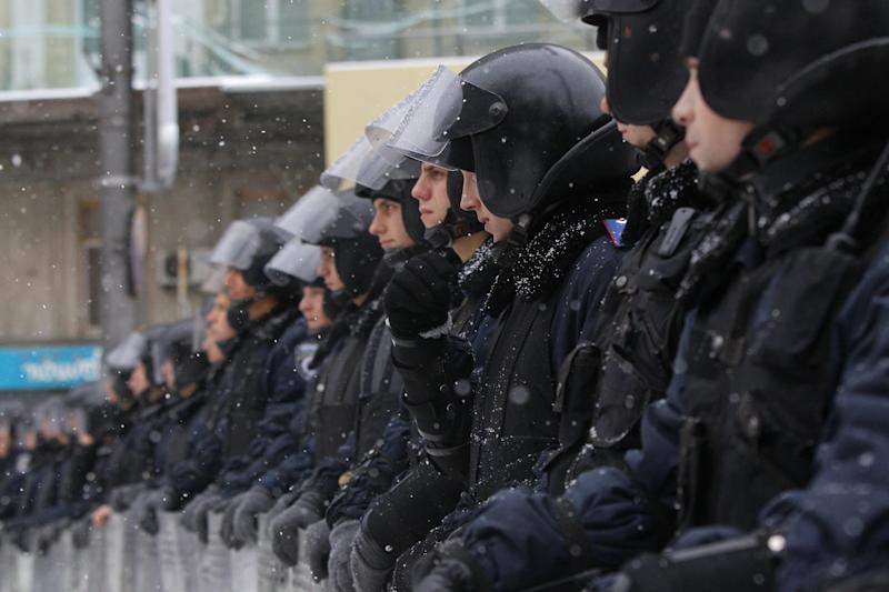 Ukrainian riot police block the road next to Pro-European Union activists gathered on the Independence Square in Kiev, Ukraine, Monday, Dec. 9, 2013. The policemen, wearing helmets and holding shields, formed a chain across Kiev's main street outside the city building. Organizers called on protesters to vacate the city hall and the other building which the opposition had used as its headquarters. (AP Photo/Sergei Grits)
