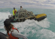 In this April 11, 2021 photo provided by Matt Saunter, Kevin O'Brien and Tate Wester remove a boatload of fishing nets from Kure Atoll in the Northwestern Hawaiian Islands. A crew has returned from the remote Northwestern Hawaiian Islands with a boatload of marine plastic and abandoned fishing nets that threaten to entangle endangered Hawaiian monk seals and other marine animals on the tiny, uninhabited beaches stretching for more than 1,300 miles north of Honolulu. (Matt Saunter, Papahānaumokuākea Marine Debris Project via AP)