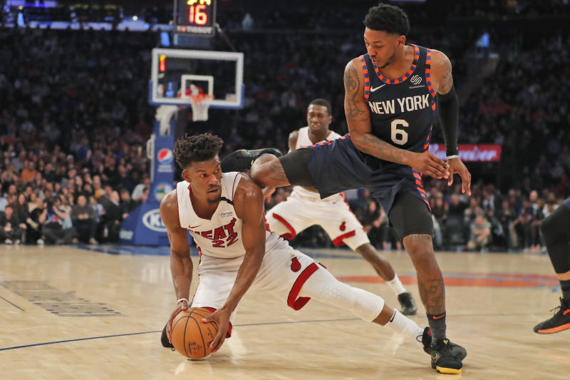 New York Knicks' Elfrid Payton, right, jumps over Miami Heat's Jimmy Butler as they scramble for a loose ball during the first half of the NBA basketball game, Sunday, Jan. 12, 2020, in New York. (AP Photo/Seth Wenig)