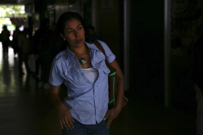 A woman tries to walk out of a building during a blackout in Caracas June 27, 2014. A blackout cut power to much of Venezuela on Friday, snarling traffic in the capital Caracas and other major cities as authorities scrambled to restore electricity after the outage, which twice interrupted a presidential broadcast. REUTERS/Carlos Garcia Rawlins (VENEZUELA - Tags: POLITICS ENERGY)