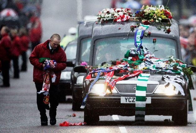 BELFAST, UNITED KINGDOM - DECEMBER 03:  A man removes scarves from the bonnet of a hearse as the funeral procession of footballer George Best drives along Prince Of Wales Avenue in the grounds of Stormont Parliament building on December 03, 2005 in Belfast, Northern Ireland. The former Manchester United and Northern Ireland international player died aged 59 from multiple organ failure at Cromwell Hospital, London on November 25.  (Photo by Andrew Parsons/PA-Pool/Getty Images) (Photo: Pool via Getty Images)