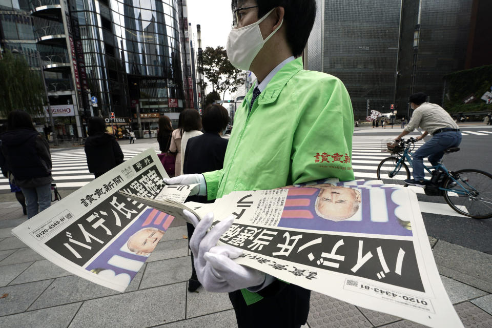 "An employee of Yomiuri newspaper distributes passers-by the extra newspaper reporting on President-elect Joe Biden's win in the U.S. presidential election, in Tokyo Sunday, Nov. 8, 2020. The headline reads: ""Mr. Biden assured of win."" (AP Photo/Eugene Hoshiko)"