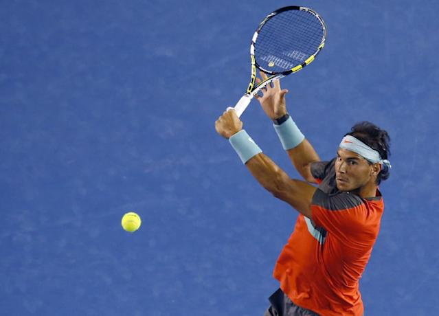 Rafael Nadal of Spain makes a backhand return to Gael Monfils of France during their third round match at the Australian Open tennis championship in Melbourne, Australia, Saturday, Jan. 18, 2014.(AP Photo/Eugene Hoshiko)