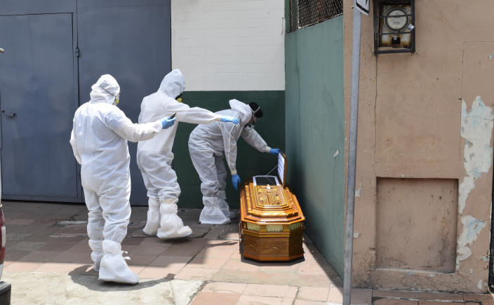 A brigade wearing a biosafety suit to protect from coronavirus retire a coffin with a body left outside a house in Guayaquil, Ecuador, Monday, April 6, 2020. Guayaquil, a normally bustling city that has become a hot spot in Latin America as the coronavirus pandemic spreads, has untold numbers dying of unrelated diseases that can't be treated because hospitals are overwhelmed. (AP Photo/Edison Choco)