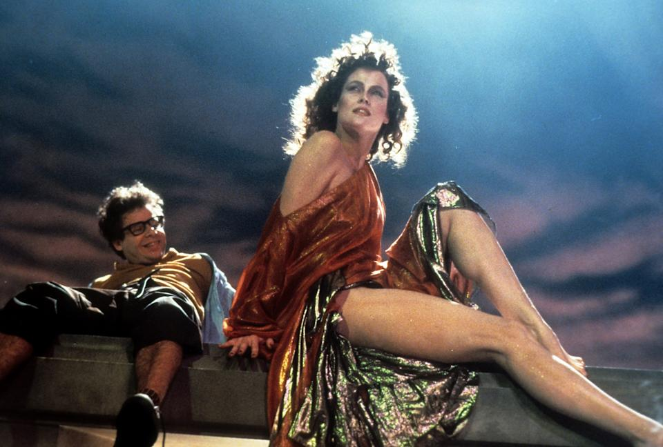 A smiling Rick Moranis looking up at Sigourney Weaver in a scene from the film 'Ghostbusters', 1984. (Photo by Columbia Pictures/Getty Images)