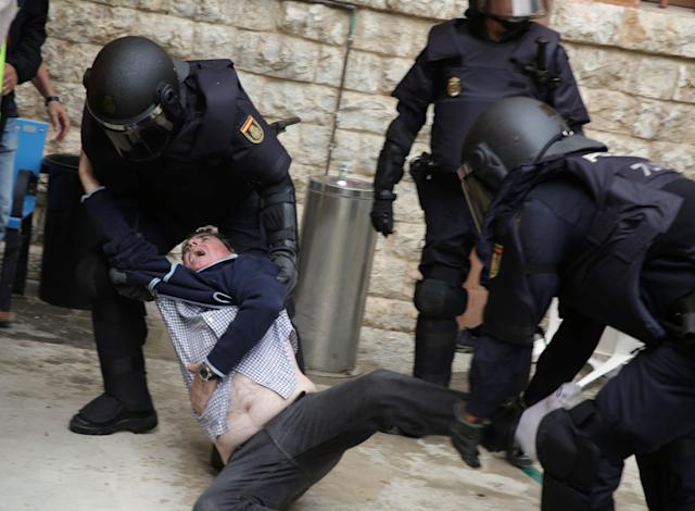 <p>Spanish police scuffle with a man outside a polling station for the banned independence referendum in Tarragona, Spain, Oct. 1, 2017. (Photo: David Gonzalez/Reuters) </p>