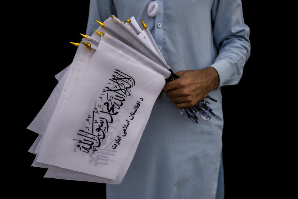A street vendor selling Taliban flags waits for customers outside the American embassy compound in Kabul, Afghanistan, Saturday, Sept. 11, 2021. (AP Photo/Bernat Armangue)
