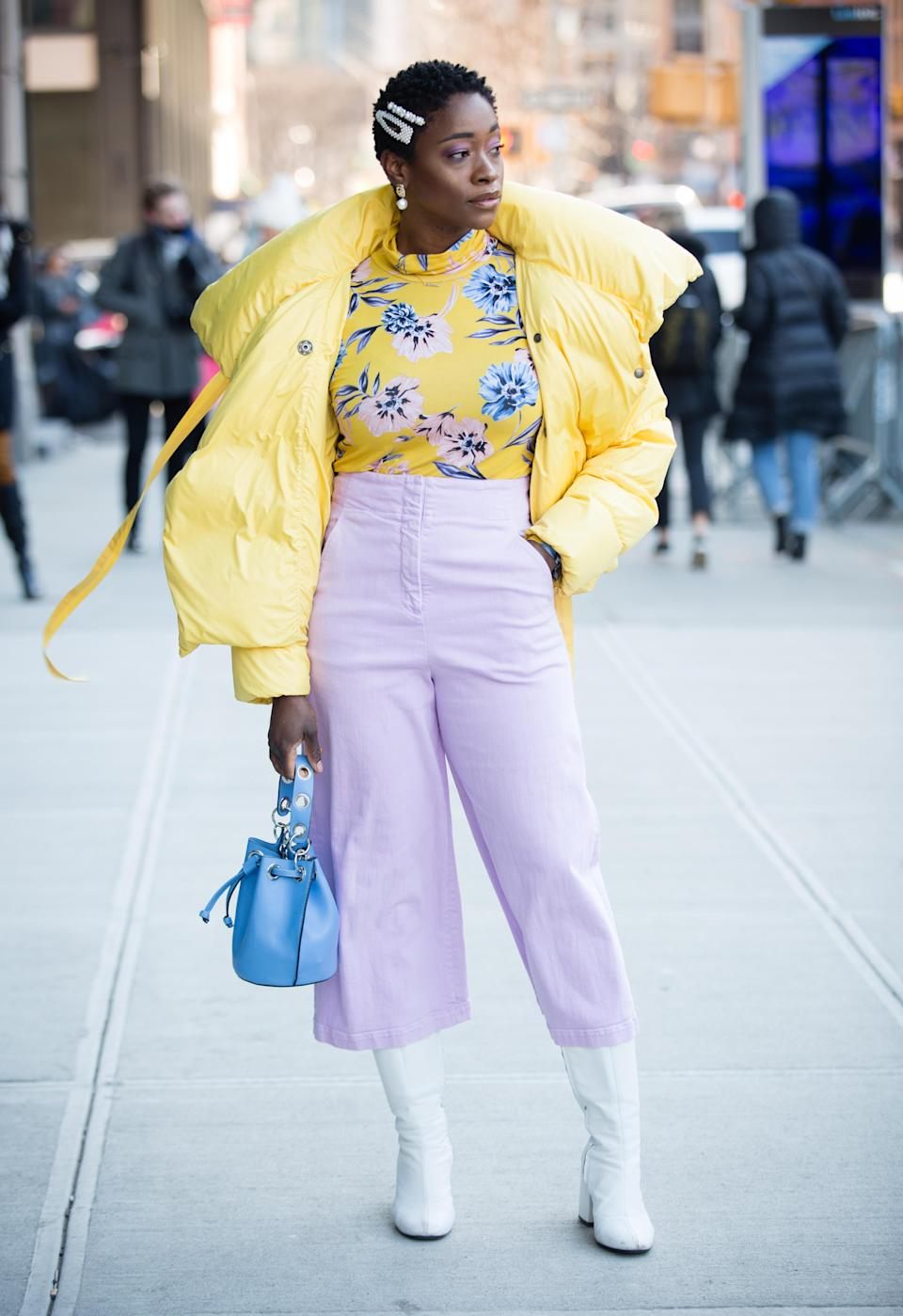 <p>A guest poses outside of the Son Jung Wang show wearing a yellow coat, yellow floral print shirt, light purple pants, white shoes and holding a blue bag. <em>[Photo: Getty]</em> </p>