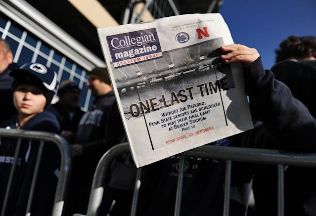 "STATE COLLEGE, PA - NOVEMBER 12: A child reads a newspaper that reads ""One Last Time"" before the Penn State against Nebraska football game at Beaver Stadium on November 12, 2011 in State College, Pennsylvania. Head football coach Joe Paterno was fired amid allegations that former Penn State defensive coordinator Jerry Sandusky was involved with child sex abuse. Penn State is playing their final home football game against Nebraska. (Photo by Patrick Smith/Getty Images)"