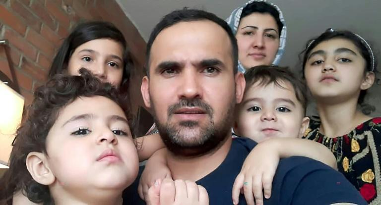 This August 17, 2021, image, courtesy of Mohammad Ehsan Saadat, shows him posing with his wife and children in Toronto