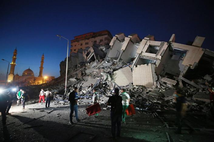 People mill about a collapsed building