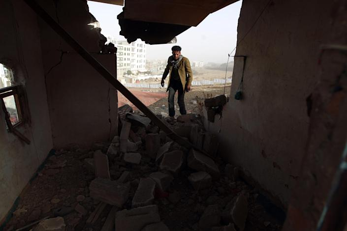 A Yemeni man walks amid the debris inside a heavily damaged house near the presidential palace in Sanaa on January 20, 2015, following fierce clashes between Huthi militiamen and the presidential guard the previous day (AFP Photo/Mohammed Huwais)