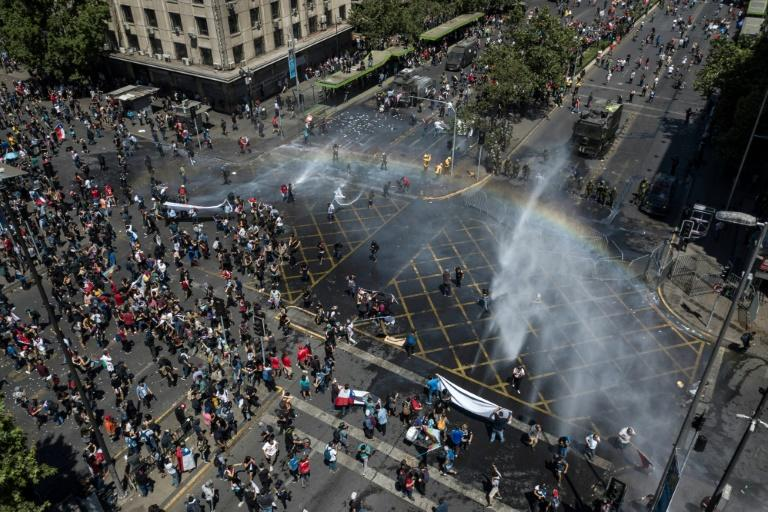 Riot police use water cannons on demonstrators in Santiago, on the sixth straight day of street violence in Chile, which has left at least 18 people dead (AFP Photo/Javier TORRES)