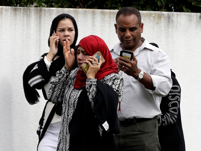 People wait outside a mosque in central Christchurch where many people were killed in two mass shootings in New Zealand on March 15, 2019.