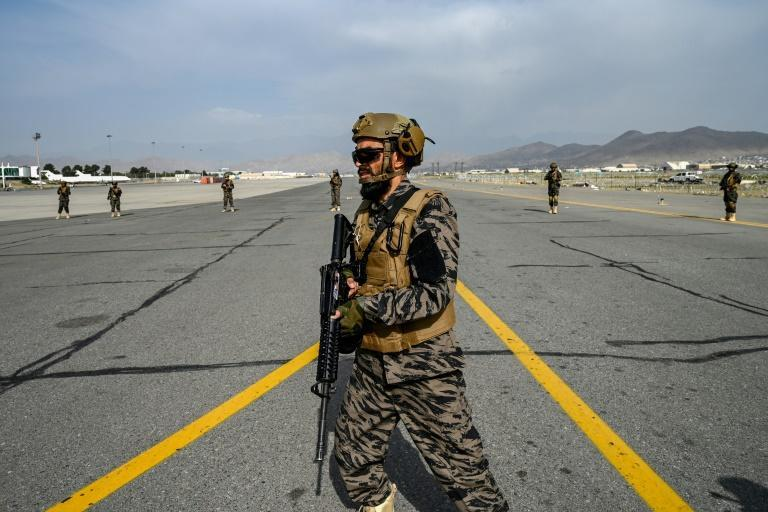 Members of the Taliban Badri 313 military unit walk on the tarmac as they secure the airport premises in Kabul on August 31, 2021 after the US withdrawal (AFP/WAKIL KOHSAR)