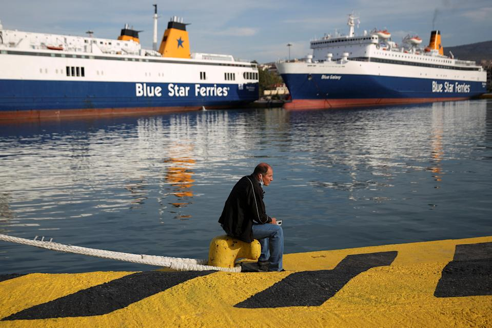 A man sits next to a moored passenger ferry during a 24-hour general strike at the port of Piraeus