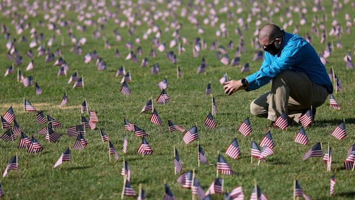 Chris Duncan, whose 75 year old mother Constance died from Covid, seen at September memorial among small US flags to commemorate the Covid dead