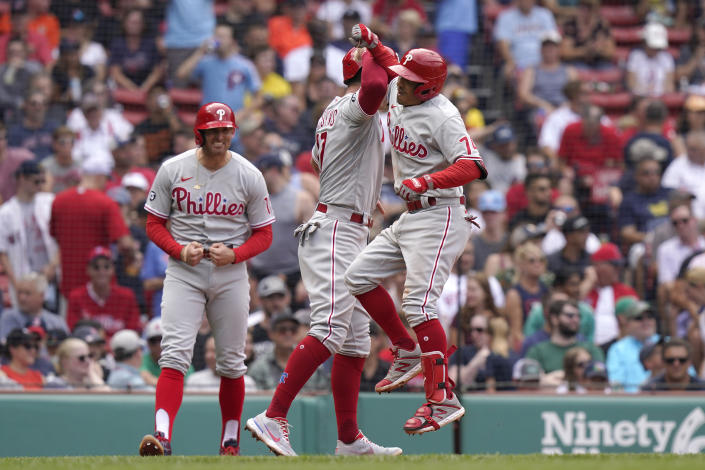 Philadelphia Phillies' Ronald Torreyes, right, celebrates his three-run home run with Rhys Hoskins, center, and Brad Miller, left, in the fourth inning of a baseball game against the Boston Red Sox, Sunday, July 11, 2021, in Boston. (AP Photo/Steven Senne)