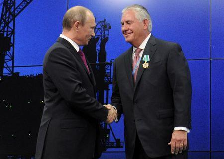 FILE PHOTO: Russian President Putin shakes hands with Exxon Mobil CEO Tillerson during a ceremony awarding heads and employees of major energy companies in St. Petersburg