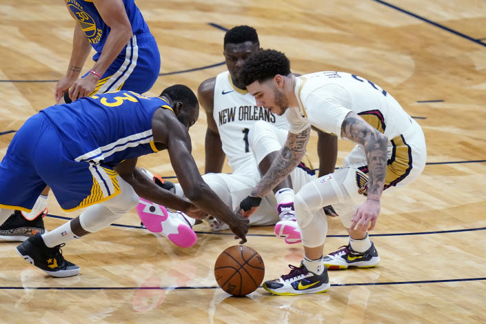 Golden State Warriors forward Draymond Green (23) and New Orleans Pelicans guard Lonzo Ball (2) battle for a loose ball in the second half of an NBA basketball game in New Orleans, Monday, May 3, 2021. (AP Photo/Gerald Herbert)
