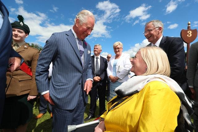 The Prince of Wales greets guest Penny Redman at the Castle Coole garden party