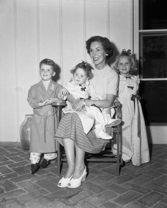 """<div class=""""caption-credit""""> Photo by: Courtesy of Corbis</div><div class=""""caption-title""""></div>Actress Maureen O'Sullivan with three of her children, including a shy four-year-old Mia Farrow hiding behind her mother in 1950."""