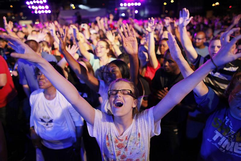 """Dharma Bohall, 13, extends her arms in prayer during the America for Jesus prayer rally, Friday Sept. 28, 2012, on Independence Mall in Philadelphia. Christian conservatives who blame """"moral depravity"""" for everything from the recession to terrorism are converging on Philadelphia for a rally they hope will spark a religious revival as Election Day nears.  (AP Photo/ Joseph Kaczmarek)"""