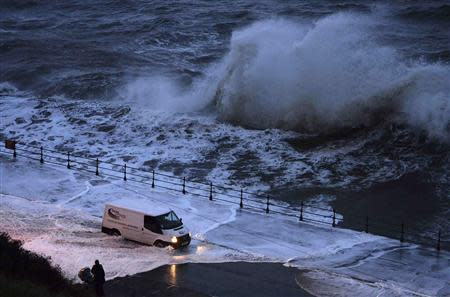 A van drives through seawater washed onto the promenade of the north bay in Scarborough, northern England December 5, 2013. REUTERS/Nigel Roddis