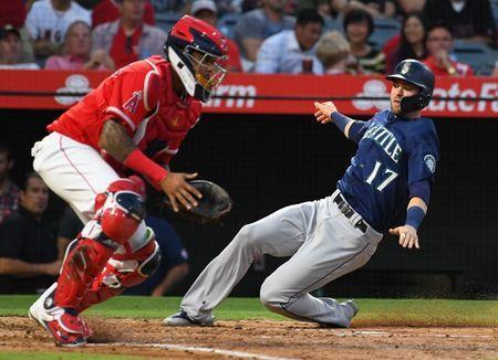 Jul 11, 2018; Anaheim, CA, USA; Seattle Mariners right fielder Mitch Haniger (17) scores against Los Angeles Angels catcher Martin Maldonado (12) on a two RBI single by Seattle designated hitter Nelson Cruz (not pictured) in the fourth inning at Angel Stadium of Anaheim. Mandatory Credit: Jayne Kamin-Oncea-USA TODAY Sports