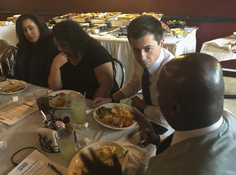 Democratic presidential candidate Pete Buttigieg, third from left, listens to Mikey Kelly as the South Bend mayor meets with black voters at a soul food restaurant in North Las Vegas, Saturday, Dec. 21, 2019. (AP Photo/Michelle L. Price)