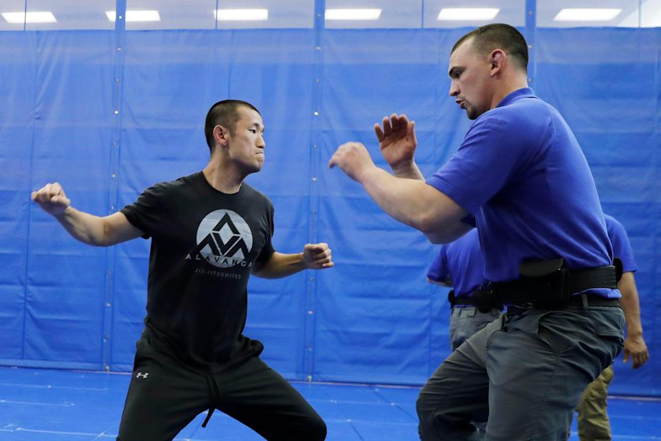 In this June 4, 2020, photo, Brandon Wilson, right, an instructor at the Washington State Criminal Justice Training Commission facility in Burien, Washington, defends against a simulated punch thrown by fellow instructor Ben Jia during a demonstration for The Associated Press on takedown and restraint techniques taught to law enforcement officers.