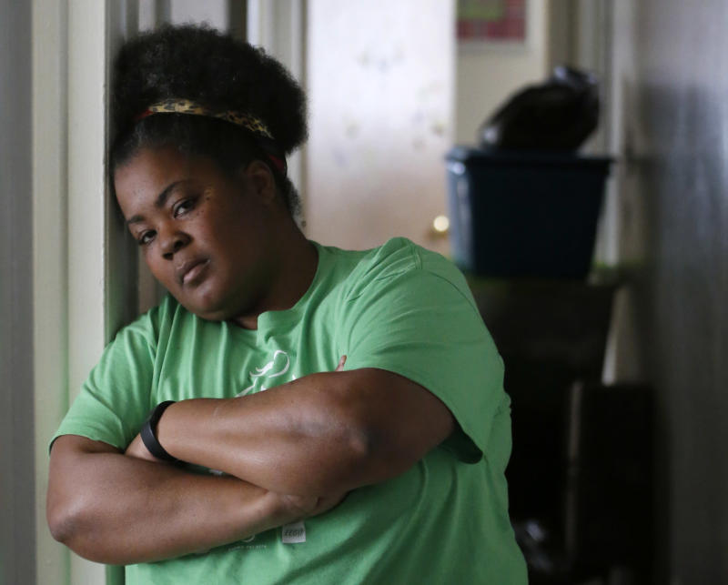 In this Thursday, March 30, 2017, photo, Tara Adams poses for a portrait in her home as boxes sit stacked in a hallway waiting for an impending move from her East Chicago, Ind., home. Adams is one of dozens of families in this former industrial town who have yet to be evacuated from a housing project ordered emptied by the mayor because of severe lead contamination.  (AP Photo/Charles Rex Arbogast)