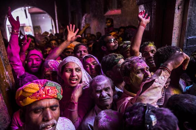 VRINDAVAN, INDIA - MARCH 26: Hindu devotees celebrate during Holi with colored powers at the Banke Bihari temple on March 26, 2013 in Vrindavan, India. The tradition of playing with colors on Holi draws its roots from a legend of Radha and the Hindu God Krishna. It is believed that young Krishna was jealous of Radha's fair complexion since he himself was very dark. After questioning his mother Yashoda on the darkness of his complexion, Yashoda, teasingly asked him to colour Radha's face in which ever colour he wanted. In a mischievous mood, Krishna applied colour on Radha's face. The tradition of applying color on one's beloved is being religiously followed till date. (Photo by Daniel Berehulak/Getty Images)
