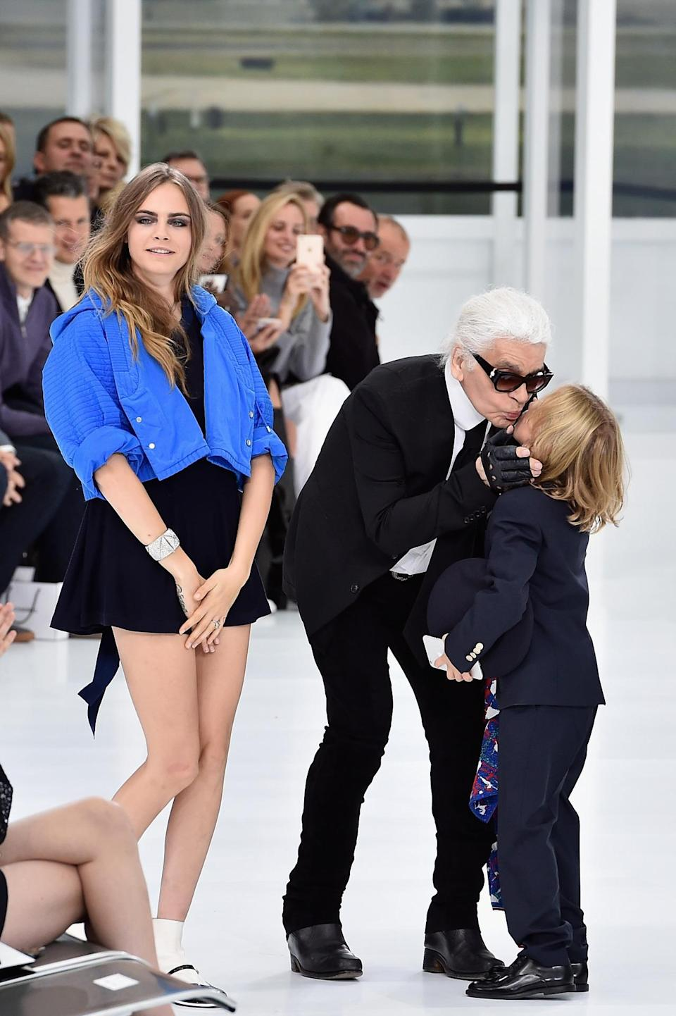 """<p>Delevingne sat front row with girlfriend Annie Clark and <a href=""""https://www.yahoo.com/style/mini-models-are-having-a-moment-first-99518037053.html"""" data-ylk=""""slk:Hudson Kroenig;outcm:mb_qualified_link;_E:mb_qualified_link;ct:story;"""" class=""""link rapid-noclick-resp yahoo-link"""">Hudson Kroenig</a>, Lagerfeld's godson (Hudson's dad walked in the show). (<i>Photo: Getty Images)</i></p>"""