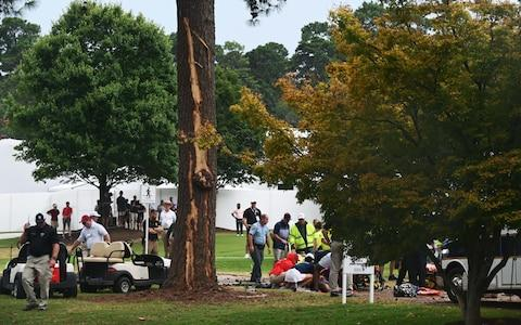 Fans are assisted by medical personnel after a lightning strike during the third round of the Tour Championship golf tournament at East Lake Golf Club - Credit: USA TODAY Sports