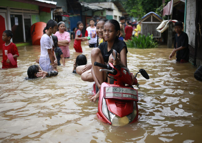 Indonesian girls sit on a motorcycle at a flooded neighborhood in Jakarta, Indonesia, Tuesday, Feb. 21, 2017. Torrential rains in the Indonesian capital have overwhelmed drains and flooded roads and thousands of homes. Floods and deadly landslides are a fact of life for Indonesians during the wet season, with other major cities suffering repeated flooding. (AP Photo/Dita Alangkara)