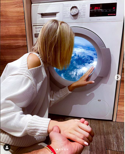 Nataly looking through the washing machine at home (Screengrab from Murad Osmann's Instagram)