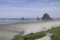 FILE - This Thursday, May 28, 2020, file photo shows Haystack Rock is seen in the distance from a balcony of The Ocean Lodge, in Cannon Beach, Ore., during the coronavirus outbreak. The sand was packed on a recent sunny day at this upscale beach town on Oregon's coast, but signs of the state's cautious approach to the pandemic were still everywhere. It was a sharp contrast to places such as Florida or Texas, where many COVID-19 restrictions have been lifted for weeks. (AP Photo/Gillian Flaccus, File)