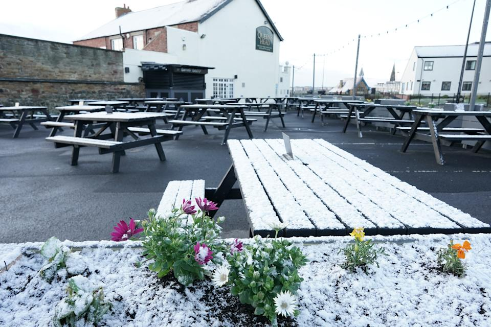 A light dusting of snow covers the outdoor seating area at the Queens Head in Cullercoats, on the North East coast, as the pub prepares to reopen its outdoor area from April 12, with customers welcome inside again from May 17. Picture date: Sunday April 11, 2021. (Photo by Owen Humphreys/PA Images via Getty Images)