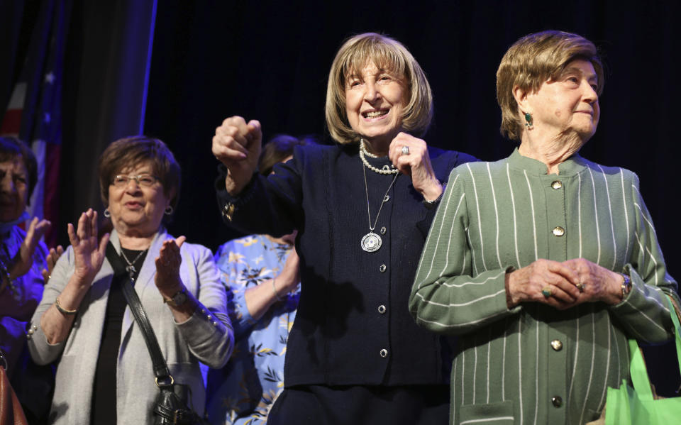 Holocaust survivors Lillian Feintuch, center, and Helen Kurtz, right, dance with other survivors on stage during a concert honoring their lives and celebrating the end of their pandemic isolation on Monday, June 14, 2021, at the Yeshivah of Flatbush theater at Joel Braverman High School in the Brooklyn borough of New York. (AP Photo/Jessie Wardarski)