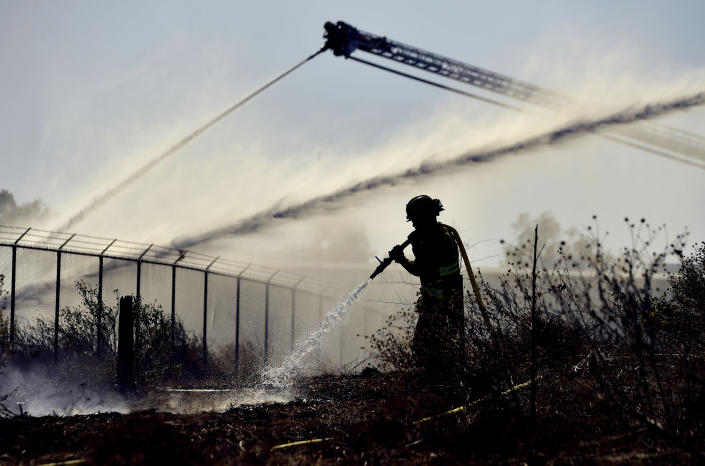 A firefighter sprays an area of a mulch and pallet fire burning out of control, fanned by Santa Ana winds in and around a recycling yard near Wilson Street and Fleetwood Drive in Riverside, Calif., Thursday, Dec. 3, 2020. Firefighters from both Riverside and San Bernardino County, along with assistance from Colton, Rialto and Riverside City Fire fought the blaze. (Will Lester/The Orange County Register via AP)
