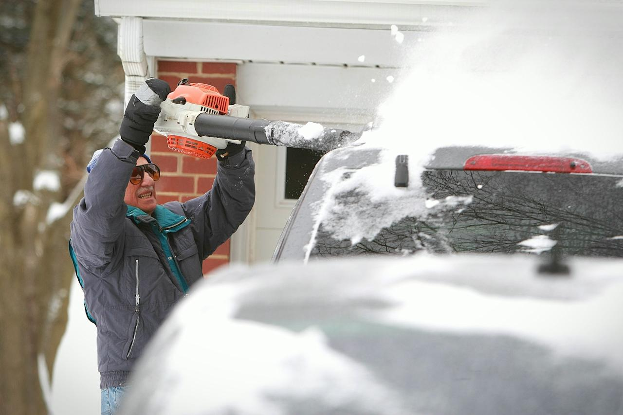 Dan Diguglielmo of Hockessin, Del., uses a blower to clear several inches of snow off of his cars Monday, March, 3, 2014. Gov. Jack Markell says he will left a state of emergency and driving warning in Kent and Sussex counties, but urged motorists to exercise caution as a winter storm continued to dump snow on the mid-Atlantic region. (AP Photo/The Wilmington News-Journal, Suchat Pederson) NO SALES