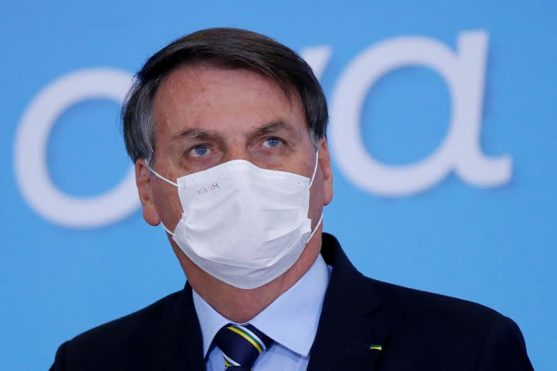 FILE PHOTO: Brazil's President Jair Bolsonaro wearing a protective mask looks on during the launching ceremony of the Plano Safra 2020/2021, action plan for the agricultural sector, in Brasilia