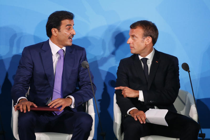 France's President Emmanuel Macron, right, talks with Qatar's Emir Sheikh Tamim bin Hamad Al-Thani before addressing the Climate Action Summit in the United Nations General Assembly, at U.N. headquarters, Monday, Sept. 23, 2019. (AP Photo/Jason DeCrow)