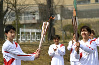 Japanese torchbearer Azusa Iwashimizu, right, a member of Japan women's national football team, passes the Olympic flame to high school student Asato Owada, left, at a torch kiss point during the Tokyo 2020 Olympic Torch Relay grand start outside J-Village National Training Center in Naraha, Fukushima prefecture, northeastern Japan, Thursday, March 25, 2021. The torch relay for the postponed Tokyo Olympics began its 121-day journey across Japan on Thursday and is headed toward the opening ceremony in Tokyo on July 23. (Philip Fong/Pool Photo via AP)