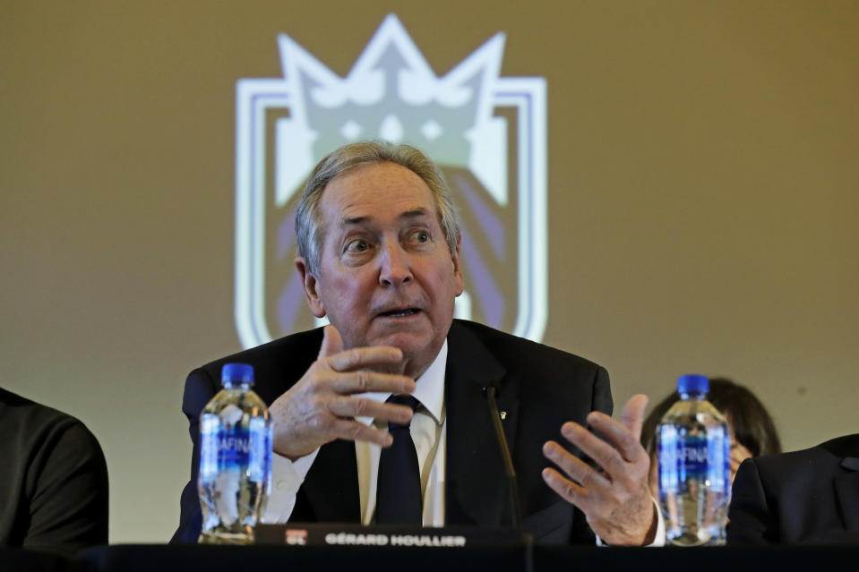 OL Groupe's Gerard Houllier sits in front of the Rein FC team logo as he speaks, Thursday, Dec. 19, 2019, during a news conference to announce that OL Groupe, the parent company of Olympique Lyonnais, is buying the National Women's Soccer League's Reign FC team in a transaction expected to close in January 2020. Reign FC will continue to play its home games at Cheney Stadium, the venue it shares with the Triple-A minor league baseball team the Tacoma Rainiers. (AP Photo/Ted S. Warren)